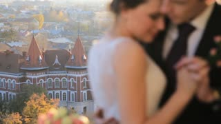 wonderful rich bride and groom look at each other on the terrace on the background at sunset on a sunny warm Lviv city Shot in slow motion  close up