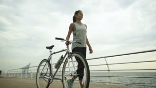 Young active brunette holding bycicle in her hand, while posing on camera.