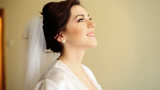 Young adorable happy bride touching her wedding dress and smile on camera.