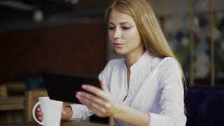Young attractive blonde businesswoman in white shirt at coffee time working on digital tablet while sitting in coffee shop