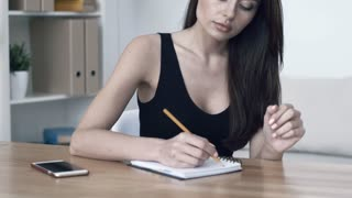 Young attractive tired, overworked and exhausted female office worker in black top and with notepad