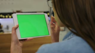 Young attractive woman using tablet with green screen sitting in the cafe, swipe pictures, news. Close-up. Chroma key