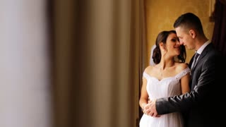 Young beautiful bride stand near the window and her handsome groom touch her shoulder. A very romantic atmosphera on the room.