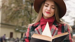 Young beautiful girl in hat reading book in city park. Slow motion.