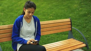 Young beautiful lady sitting on a bench holding smartphone on her hands.