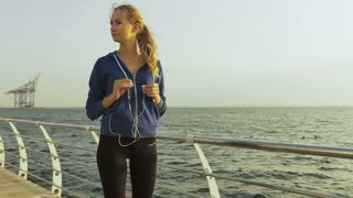 Young beautiful lady with headphones, running near the sea.