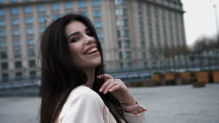 Young beautiful laughing woman walking and running, joyful and cheerful smiling on a background of the city. Girl dressed in white jacket