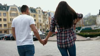Young beautiful sweet couple walking holding hands in the city, wearing white t-shirt and checkered shirt, view back