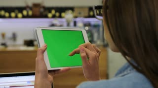 Young beautiful woman using tablet with green screen sitting in the cafe, swipe pictures. Close-up. Chroma key