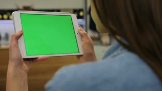 Young beautiful woman watching video on tablet with green screen in the cafe. Close-up. Chroma key. Greenscreen