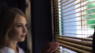 Young blonde beautiful woman in white shirt looking out the window through the louver