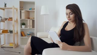 Young brunette businesswoman dressed in black siting with computer tablet on the white sofa.