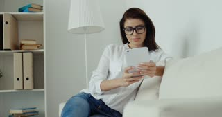 Young brunette businesswoman in white shirt, blue jeans and glasses with computer tablet siting on the white sofa.