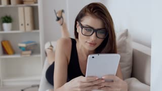 Young brunette woman in black dress and glasses lying on the couch reading on digital tablet with a smile