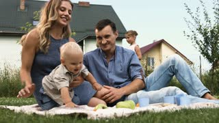 Young cheerful family with little kids having holiday with picnic at park in summer day