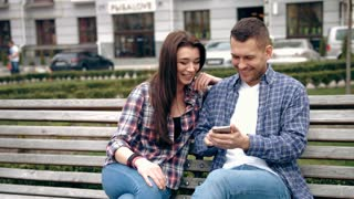Young couple sitting on bench in the city and watching on smartphone