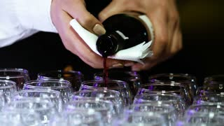Young female sommelier with beautiful nail design is pouring up transparent  glasses with wine.