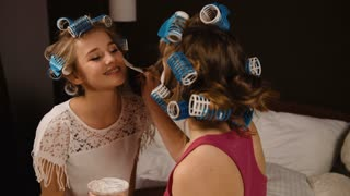 Young funny blond friend with curlers making masque on the face of her friend.