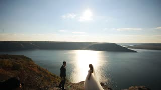 Young handsome groom in suit and the bride in a white elegant dress standing on the shore of a mountain lake.