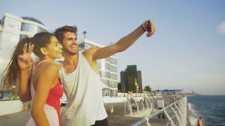 Young handsome man and his beautiful woman taking selfies after morning jog.