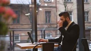 Young happy businessman with laptop in cafe