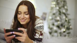 Young happy lady writing messages on her mobile phone . Beautiful Christmas decoration.