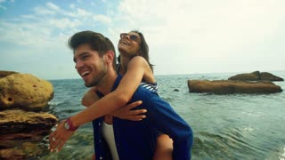 Young happy smiling man holding his beautiful woman on hands, having fun on the beach.