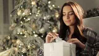 young happy surprised woman opening gift box near decorated christmas tree