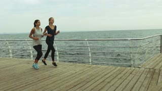 Young ladies wearing cool gym-shoes and trendy t-shirts for sport running near the sea.