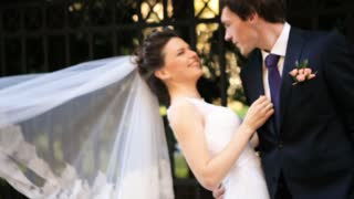 young luxury gorgeous happy bride and groom on the background of sunny city  shot in slow motion  close up