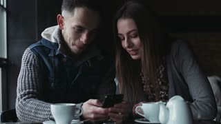 Young male and female sitting at the cafe and looking on the screen of the smartphone happy couple playing games on device and smiling to each other
