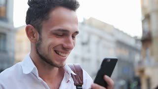 Young male person watching on a phone screen and laughing
