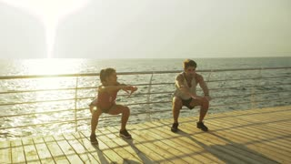 Young man and a woman squatting together on the wooden boardwalk.