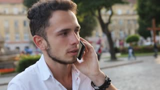 Young man have a serious talk on cellphone in the city center. Male in his 20s.