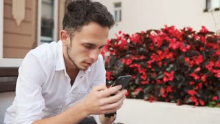 Young man in white shirt sitting on a bench and using cellphone. Hipster scrolling on smartphone.