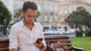 Young man sitting in square and holding his smartphone. Male in his 20s using mobile phone.