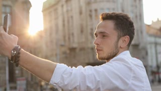 Young man taking panorama picture by using his smartphone. Handsome caucasian male in his 20s doing selfie outdoors. Guy using frontal camera on his device.