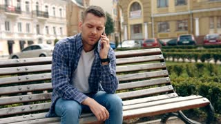 Young man talking on his mobile phone while sitting in the city