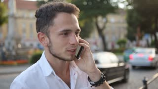 Young man talking on mobile phone in the middle of an european city center. Male in his 20s in slow motion.