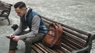 . Young man using his tablet outdoors and then put it into his brown backpack. Guy sitting on the bench within an old town and trying to hide his mobile device into the bag.