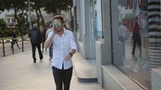 . Young man wearing sunglasses and walking through the city center and talking on telephone. Urban male in his 20s.