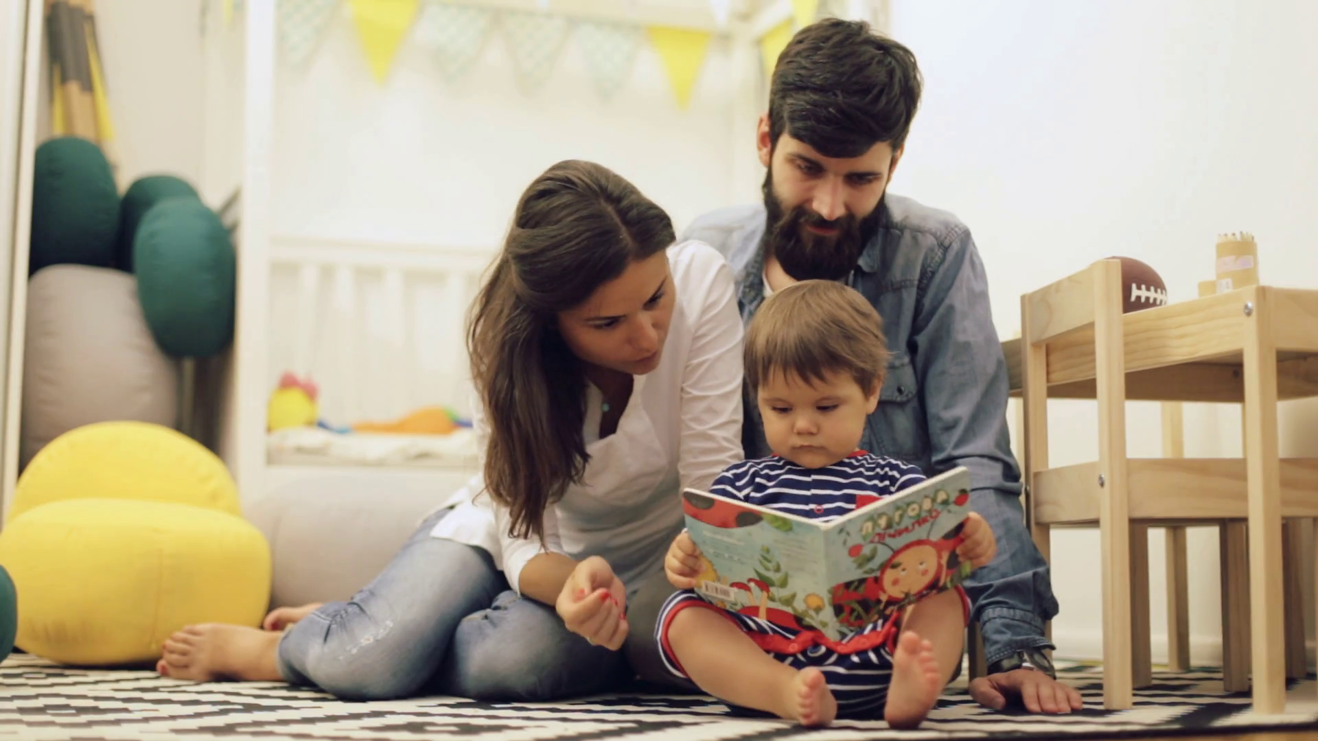 Young parents mom and dad reading children book to baby son on the floor at home Stock Video Footage - Storyblocks