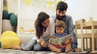 Young parents mom and dad reading children book to baby son on the floor at home