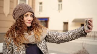 Young pretty lady wearing stylish brown hat taking selfies in the street.