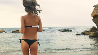Young sexy lady on black and white swimming suit running on water in a beach.
