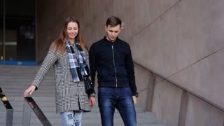 Young smiling woman and her serious handsome boyfriend moving down the stairs.