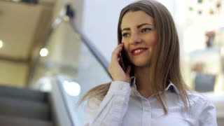 Young smiling woman is talking on her cell phone in a mall