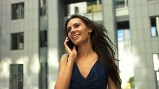 Young successful businesswoman talking on mobile phone after long day at work.