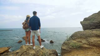 Young tanned lady with a hat and little backpack and her tall handsome boyfriend watching waves, while staying on the top of a stone.