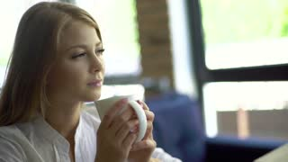 Young thoughtful beautiful woman holding coffee cup and looking away while sitting at her working place